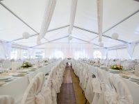 Weiß geschmücktes Festzelt bei der Hochzeit am See
